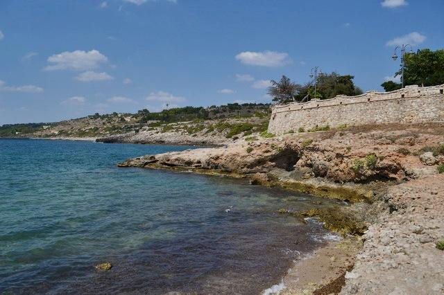 Ampia veduta sulla costa rocciosa in cui si possono notare le sfumature azzurre del suo mare cristallino che fa emergere i colori sottostanti di una rigogliosa fauna marina.