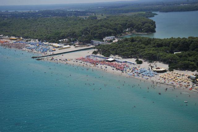 Vista dall'alto delle estese spiagge in zona Alimini, con alle spalle la profonda pineta e gli omonimi laghi.