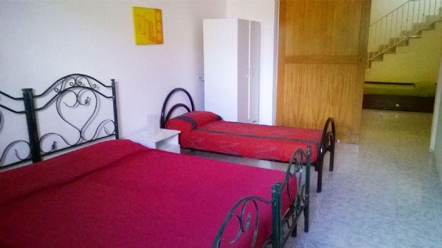camera con tre posti letto e letti in ferro battuto