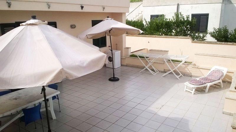 la veranda arredata con mobili da esterni e ombrelloni
