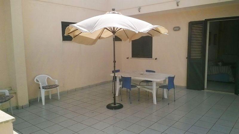 l'ombrellone, le sedie e il tavolo posti davanti alla casa vacanza