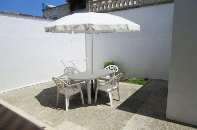 il patio sul retro con ombrellone, sedie e tavolo