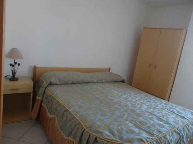 camera da letto matrimoniale con comodini e armadio