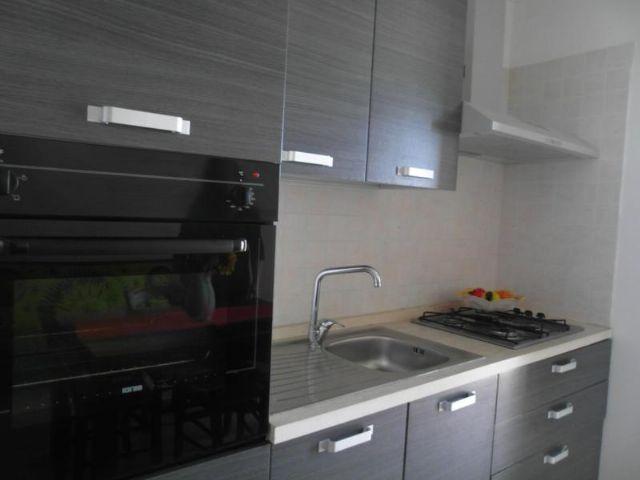 cucina componibile con cappa, mobili pensili, lavello, piano cottura e utensili da cucina