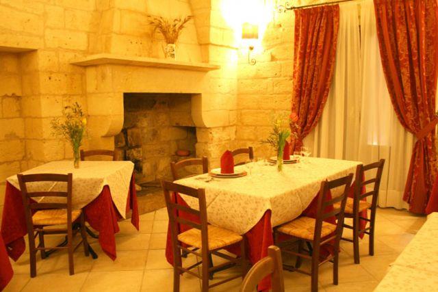 sala ristorante di Masseria Baronali con antico camino in pietra