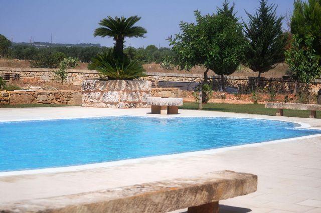 la piscina è circondata da antiche panche in pietra