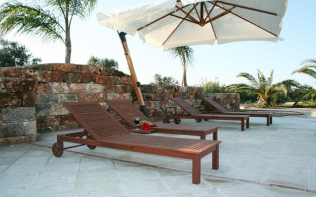 Bordo piscina attrezzato con ombrelloni e lettini