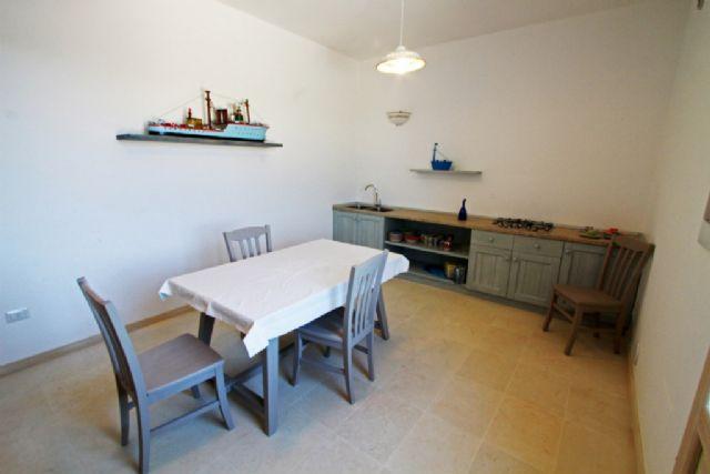 tavolo da pranzo e angolo cottura dell'appartamento trilocale
