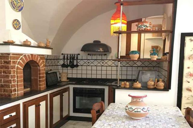 Cucina con zona pranzo, tavolo, sedie e angolo cottura in muratura