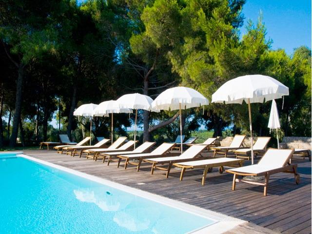 Bordo piscina attrezzato con lettini e ombrelloni