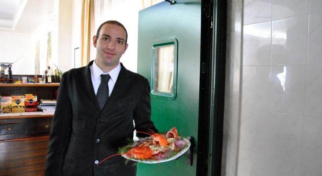 Gli chef in cucina preparano piatti a base di pesce e frutti di mare appena pescati