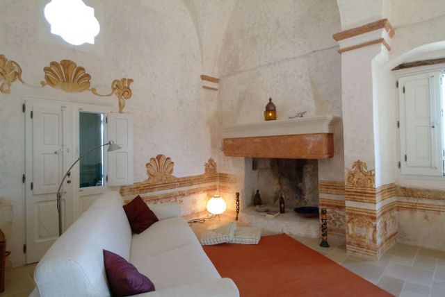 la sala relax con vecchio camino in pietra all'interno del casale