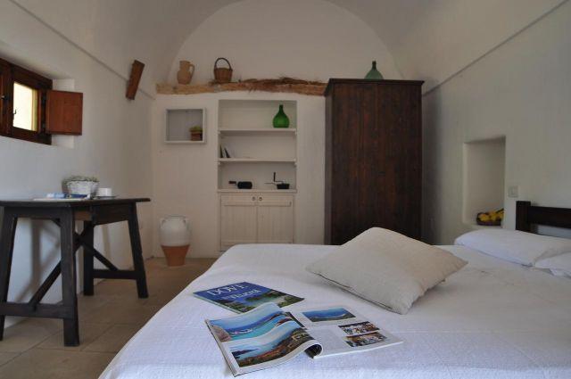 Camera con armadio in legno, ampio letto matrimoniale e scrittoio con sedia