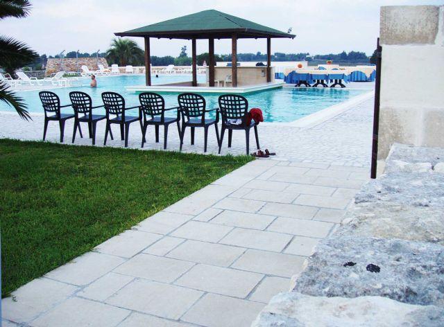 Lungo i bordi della piscina a sfioro sono disposti ombrelloni, sdraio e lettini