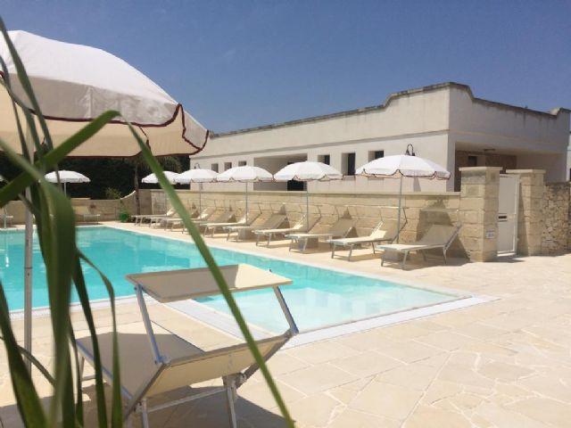la piscina con ombrelloni e lettini