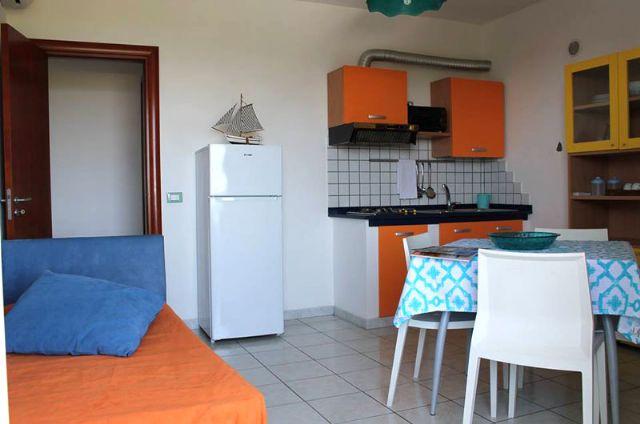 soggiorno con zona pranzo, divano e zona cottura