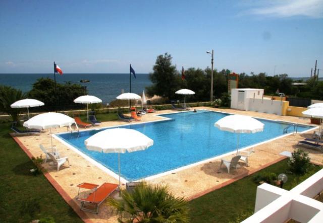 la piscina del residence solaris è attrezzata con sdraio e ombrelloni
