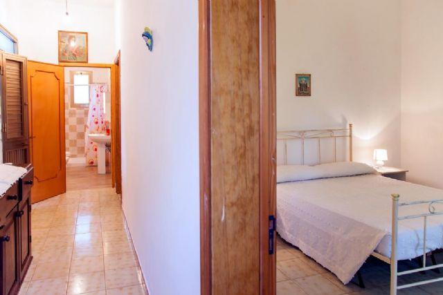 camera matrimoniale con letto in ferro battuto e corridoio